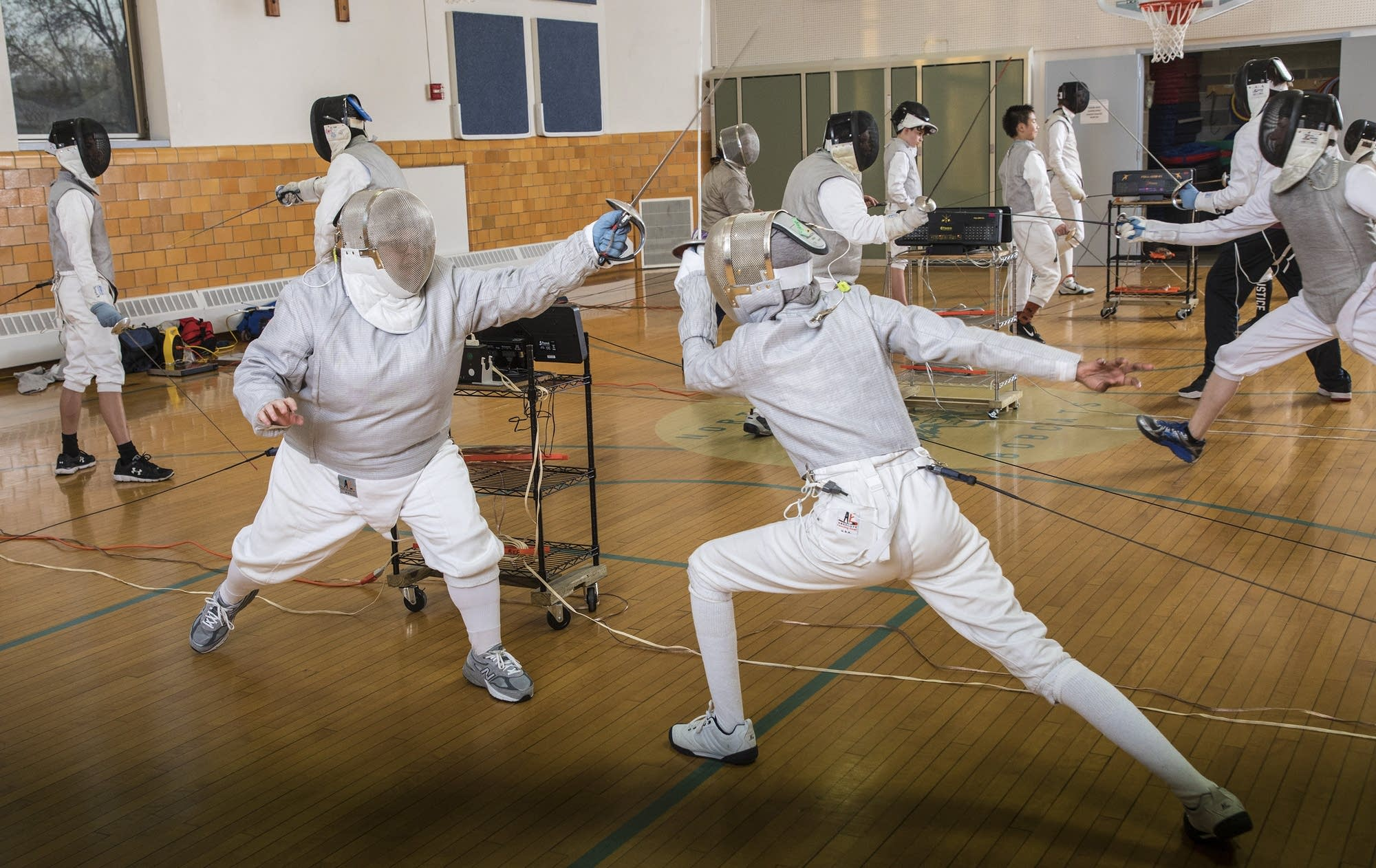 Instructor and fencing coach, Corlis Hicks, left, spars with a student.