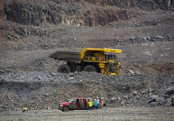 A haul truck dwarfed a pickup truck.