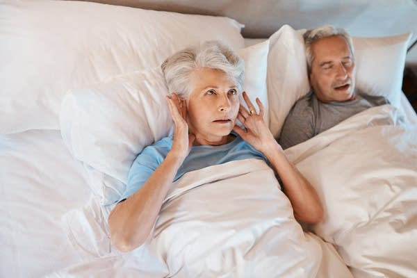 Photo of older white couple in bed, man snoring, woman frustrated