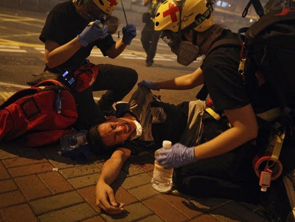 Medical workers help a protester in pain from tear gas