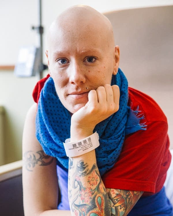 A woman with a shaved head, red shirt and blue scarf looks at the camera.