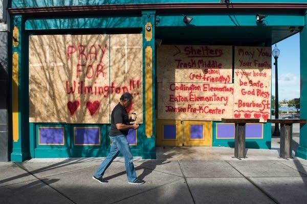 A man walks past a boarded up shop in Wilmington, N.C.