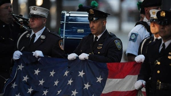 New York police officers and firefighters hold a U.S. flag