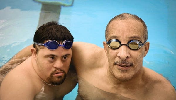 Raaj and Justin Mann pose for a portrait in the swimming pool.