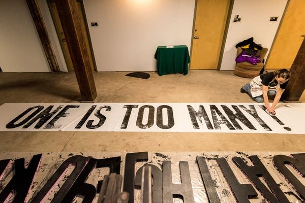 Annette Luther works on drying freshly printed banners.