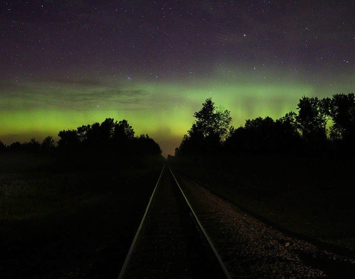 Northern lights arc across the sky above a rail line northwest of Duluth.