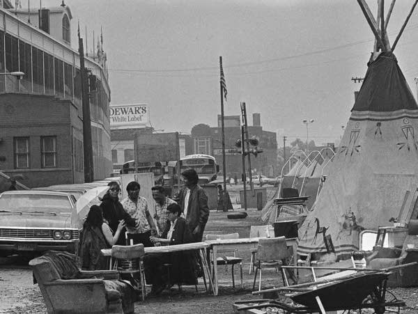 A group of protesters sit outside with cars, chairs and a shelter in view.