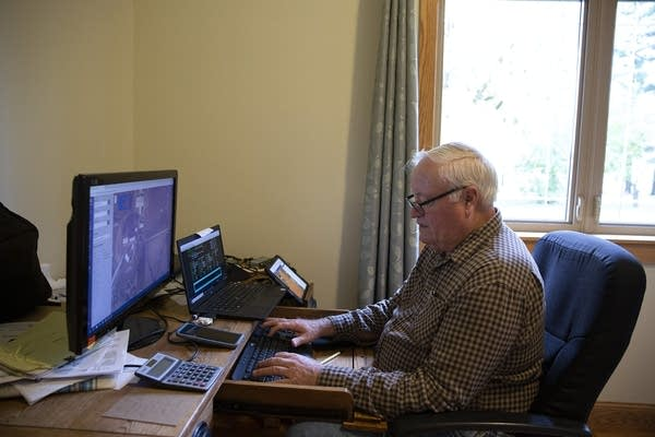 A man sits in front of a computer at a desk.