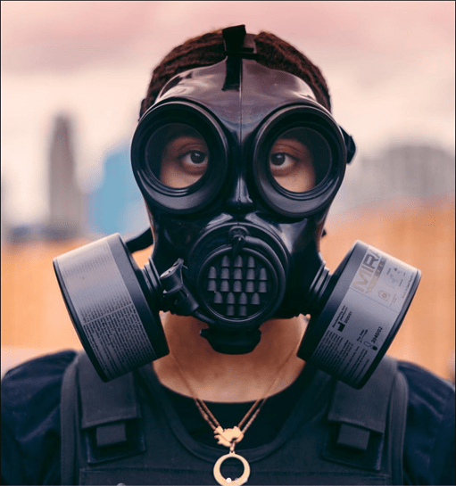A man stands with a gas mask on.