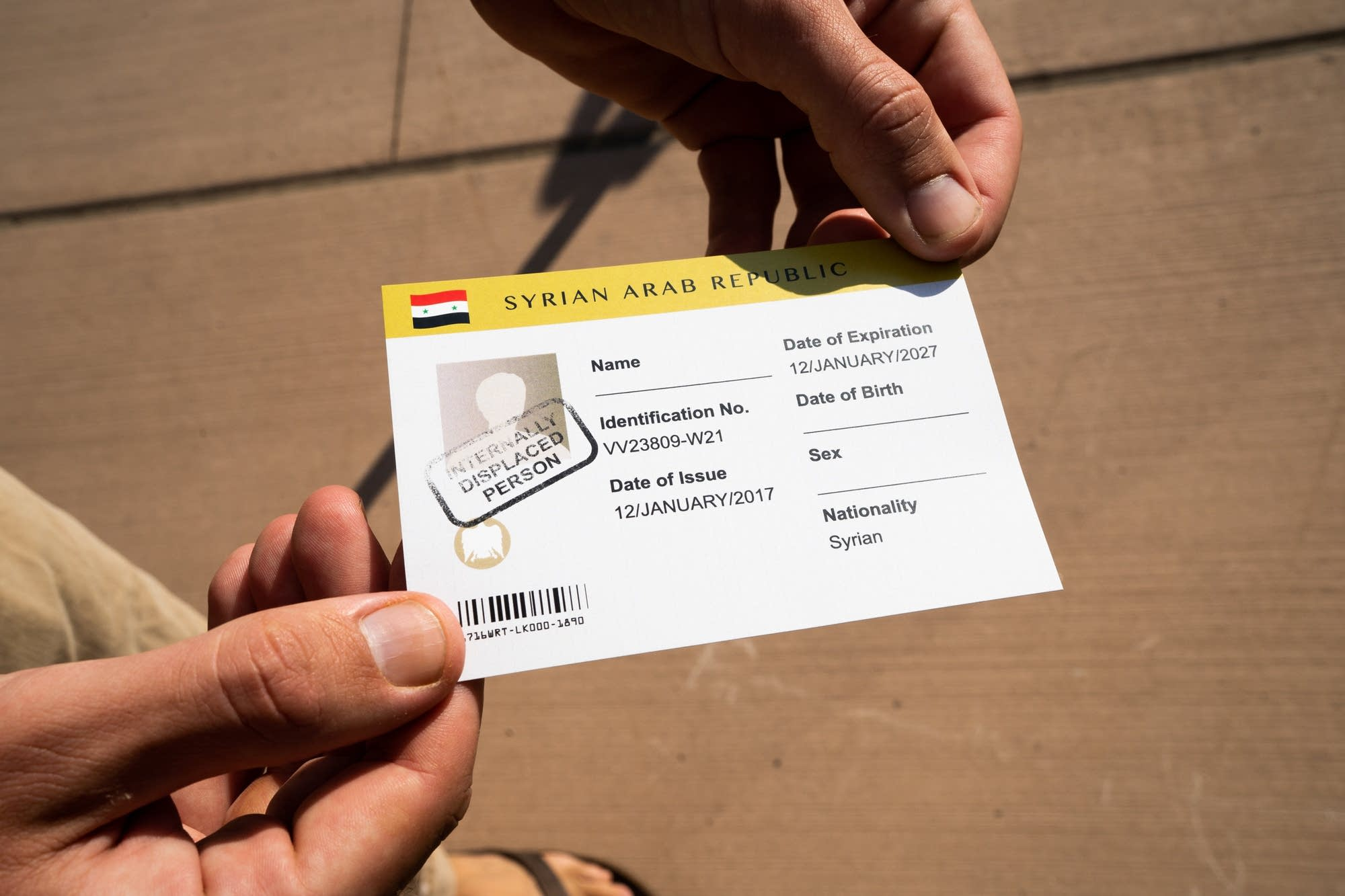 A Doctors Without Borders guide holds up a mock ID card.