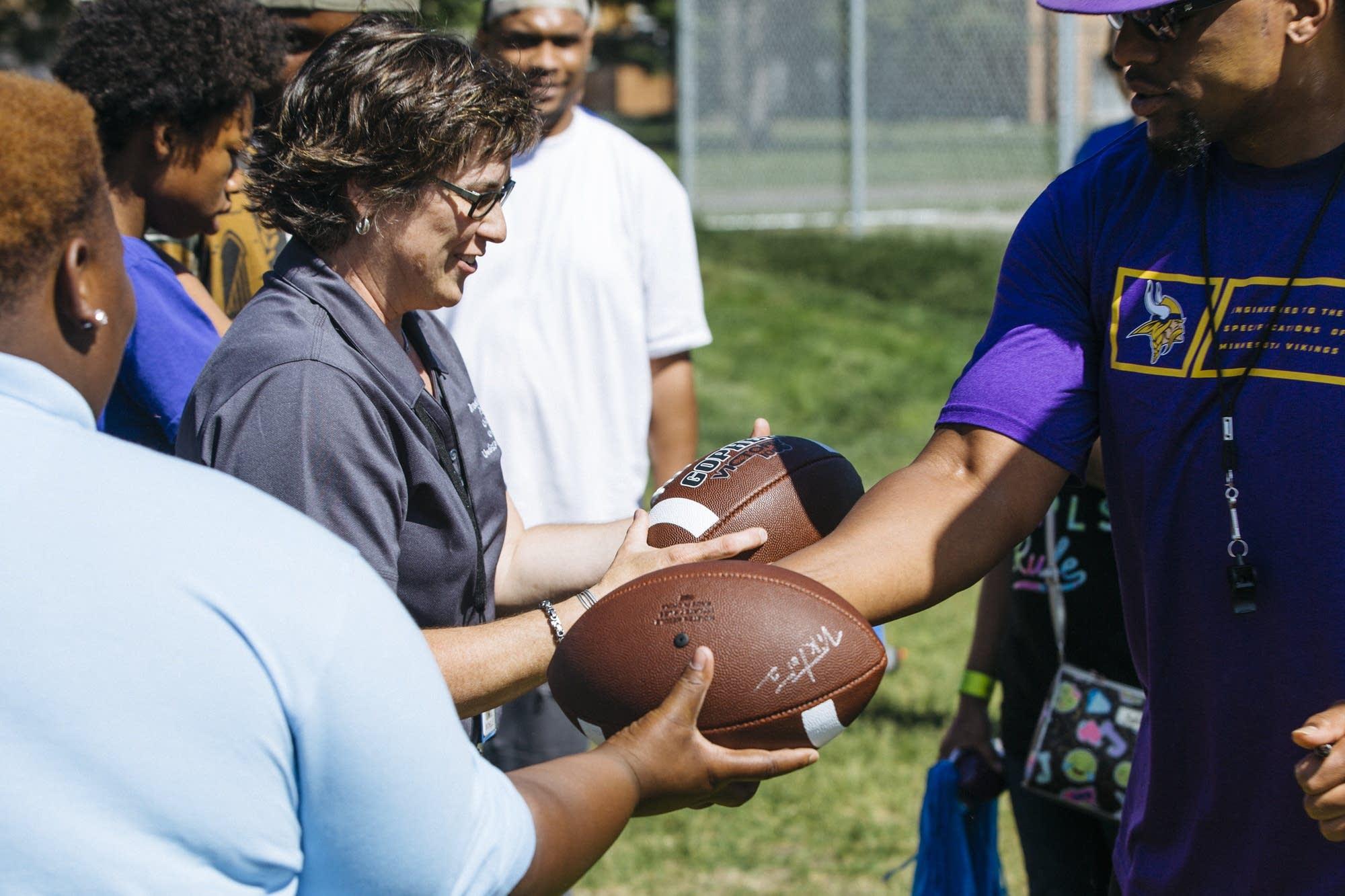E.J. Henderson hands out autographed footballs.