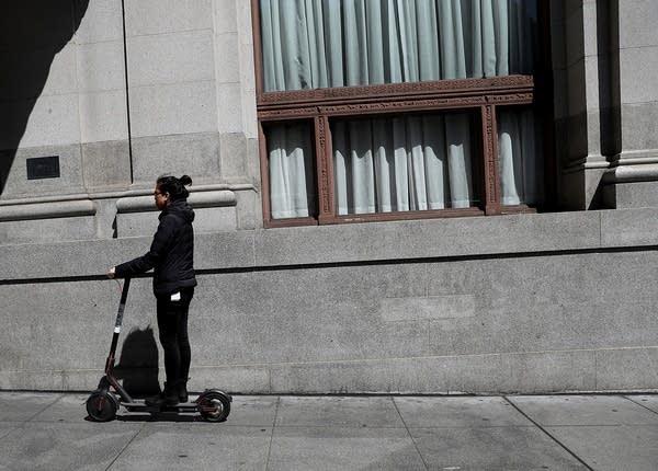 A user rides a Bird scooter in San Francisco.
