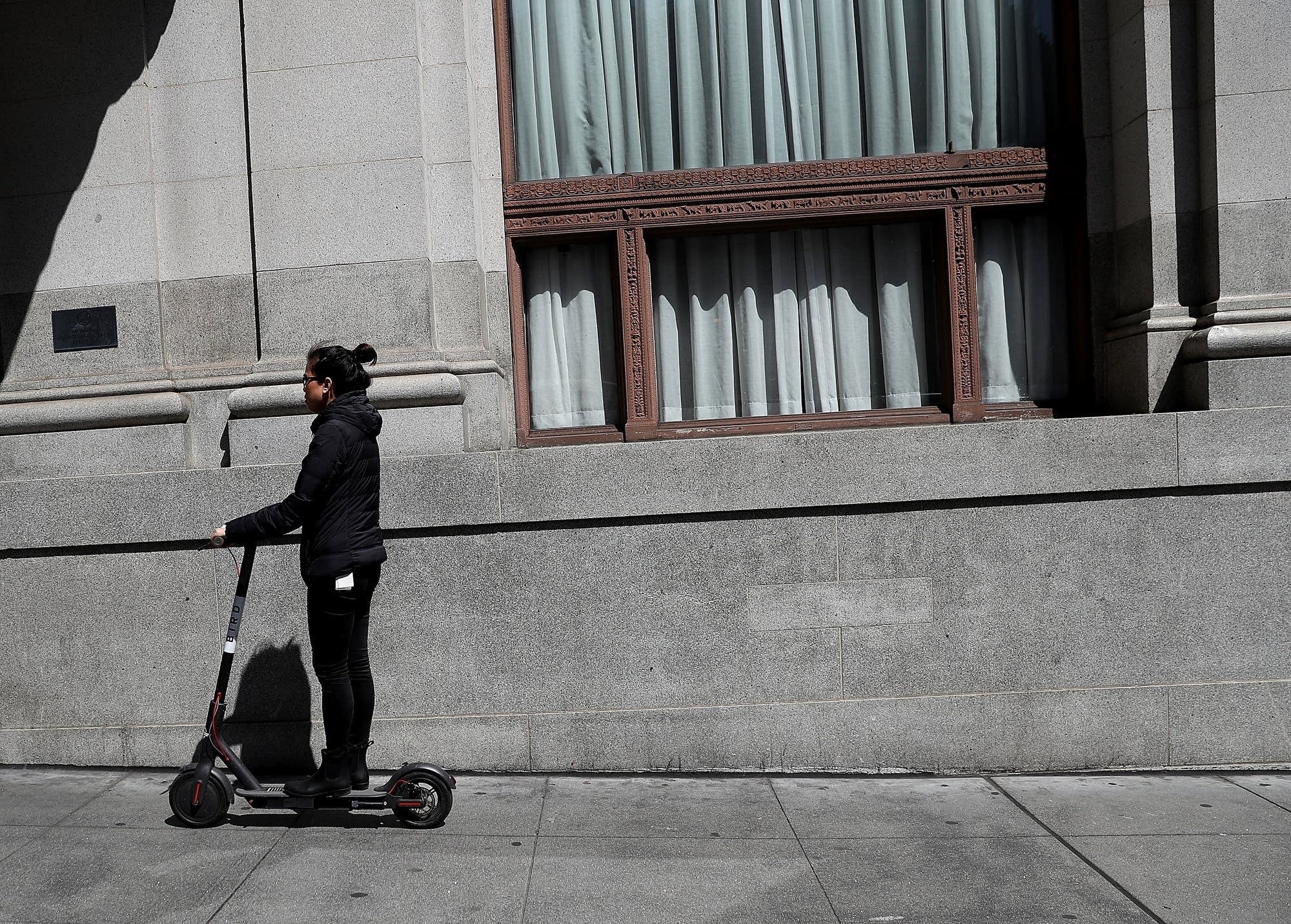 A user rides a Bird scooter in San Francisco.