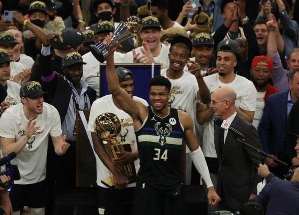 Basketball players celebrate a championship win.