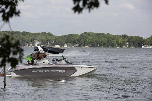 A silver and white wakeboat on the water.