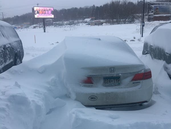Vehicles are covered by snowdrifts at a hotel