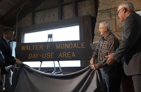 Three men unveil a wooden sign.