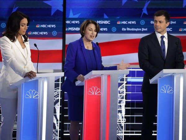 Three candidates stand on a stage for the Democratic debate.