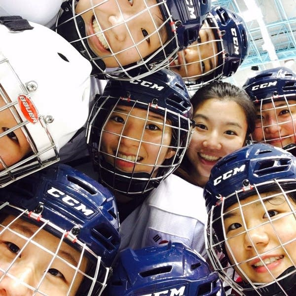A group of women wearing hockey helmets crowd together.