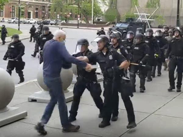 A Buffalo police officer shoves a man