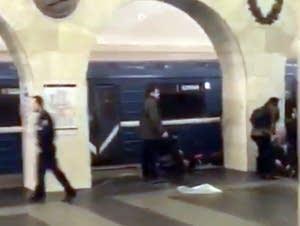 Russian police, people walk past damaged train