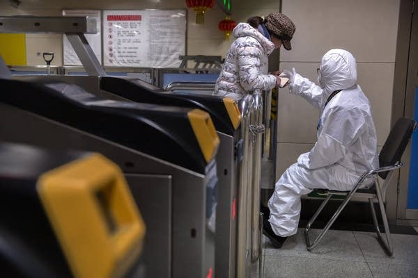 A worker wearing a hazardous materials suit gives directions.