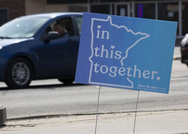 "A sign reads ""In this together."""