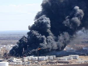 Thick smoke pours from the fire at the oil refinery.