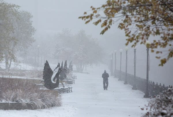 A person walks in the distance in a park with snow on the ground.