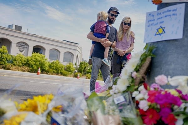 Mourners look over a makeshift memorial.