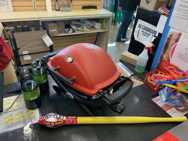 Small BBQ grill w/ fuel canisters and whiffle ball bat on store counter