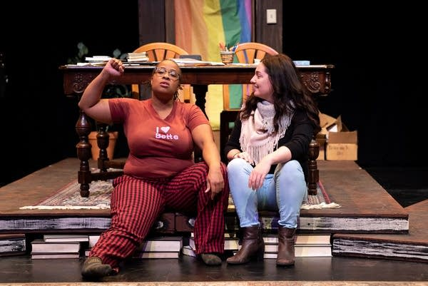 Two people sit on a stage with a desk and a rainbow flag behind them.