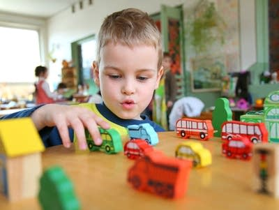 7d8645 20160923 a child plays with toy trucks in kindergarten
