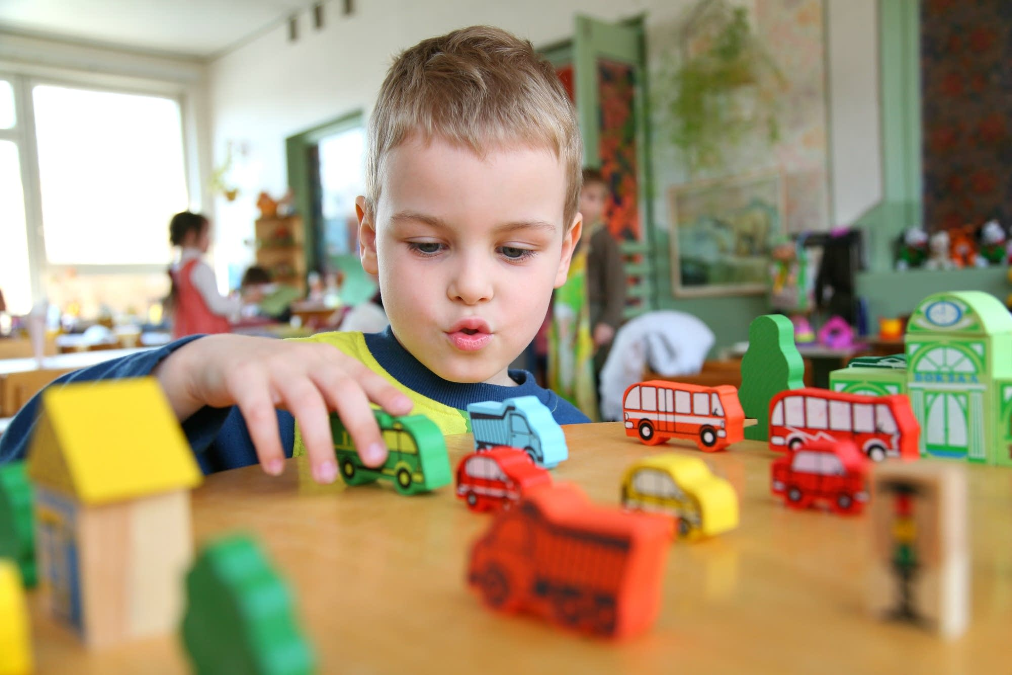 A child plays with toy trucks in kindergarten.