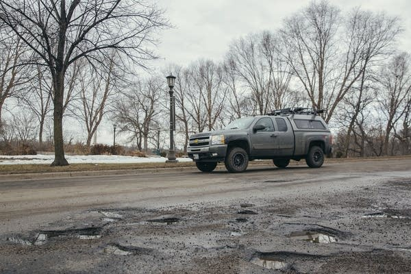 A truck cruises past potholes on Mississippi River Boulevard