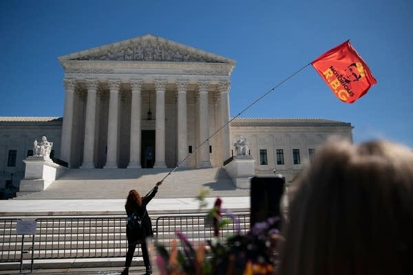 A woman waves a flag outside the Supreme Court