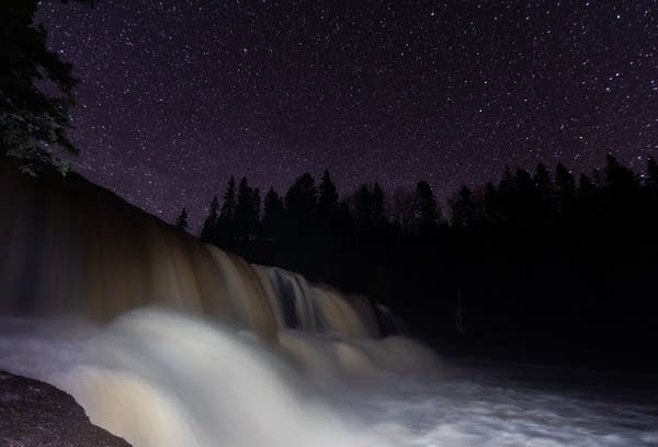 The Gooseberry Falls State Park middle falls flow under a clear night sky.
