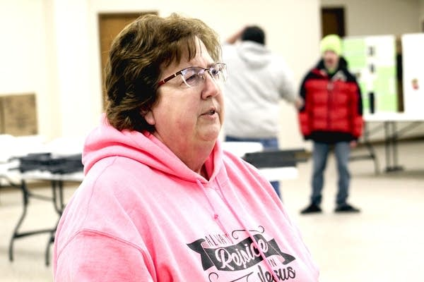 A woman wearing a pink hoodie.