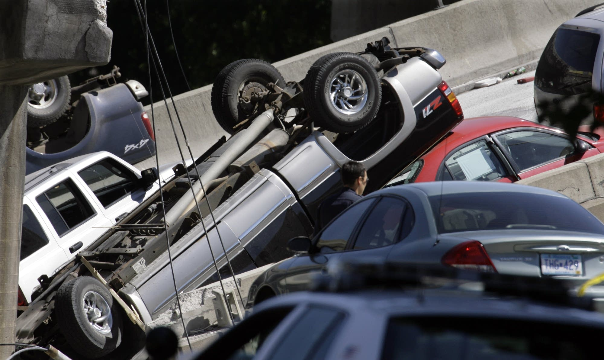 An inspector examines cars piled together at the base of the bridge.