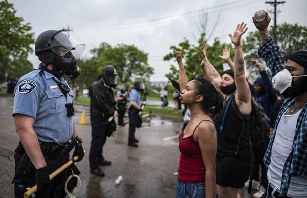 Protesters and police face each other.