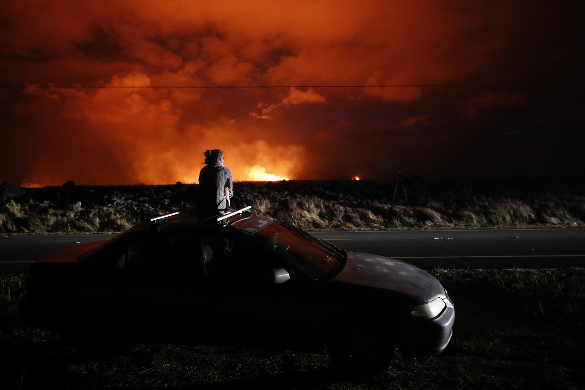 Brittany Kimball watches as lava erupts from a fissure.