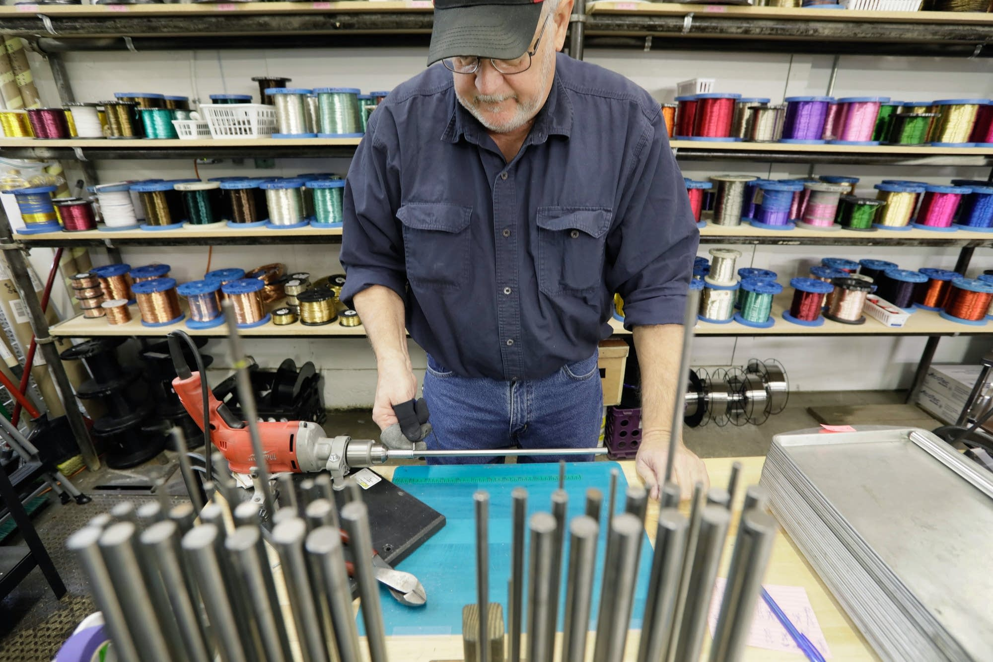 Roger Dauner uses a stationary drill to wind wire around a steel dowel.