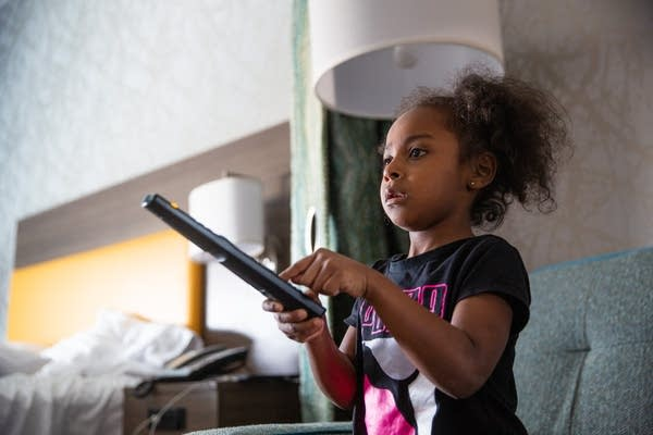 A young girl points a remote at a television.