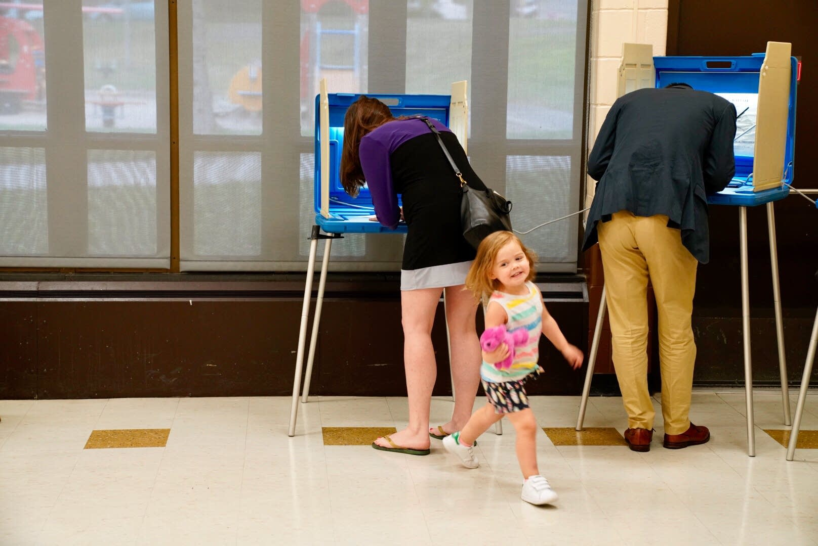 Sam, right, and Jen Rosenbaum vote with their daughter Ava.