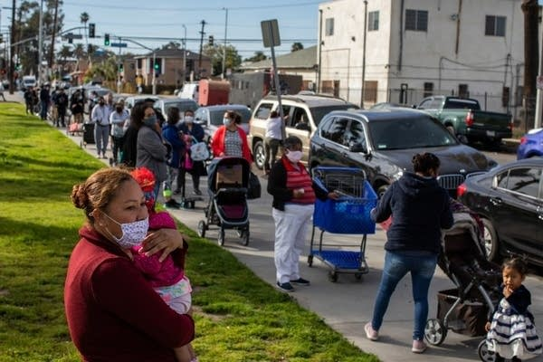 People wait in line at a food distribution event.