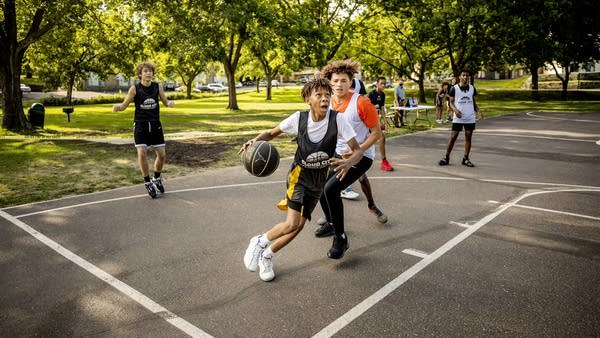 Youth play basketball at a court.