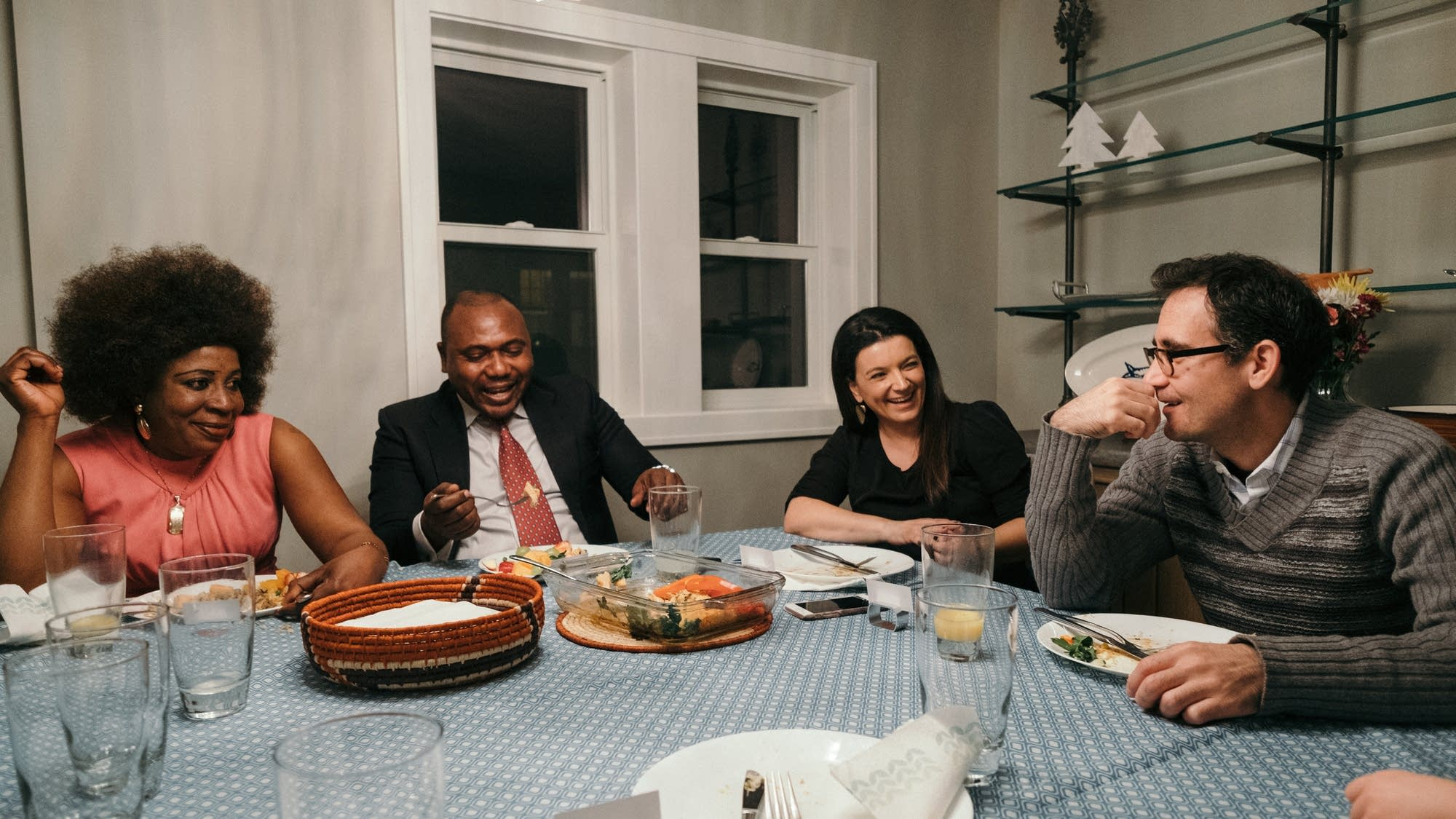 The two couples share a laugh and a meal.