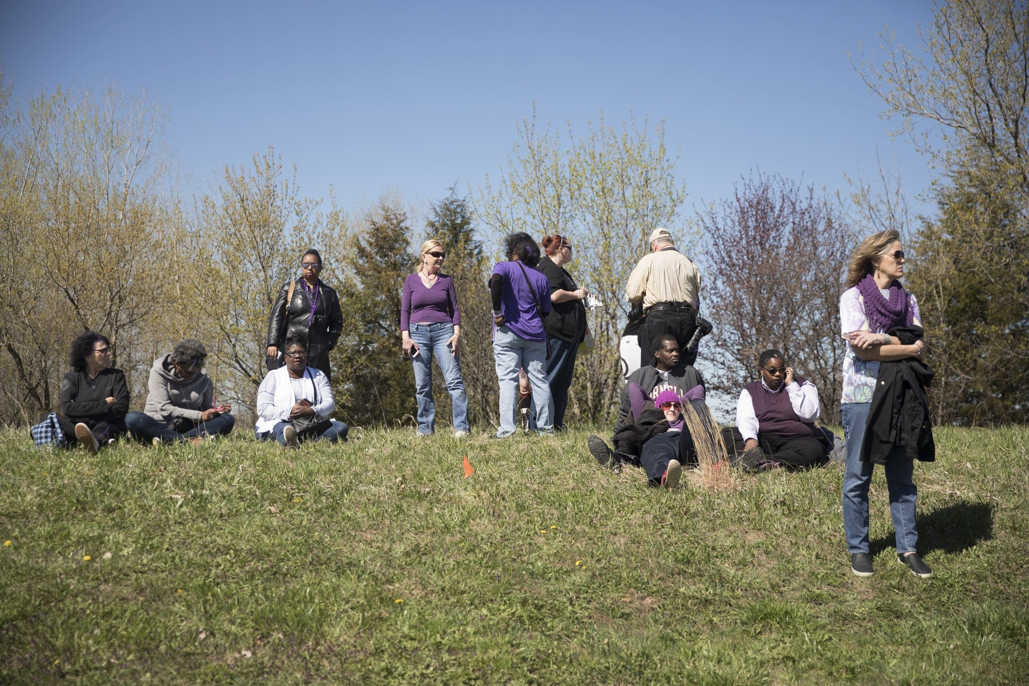 Fans of Prince sit on top of a hill across the street from Paisley Park