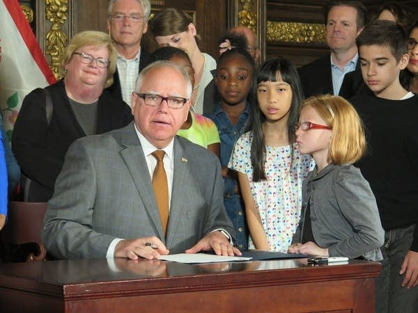 Governor Walz surrounded by children at executive order signing