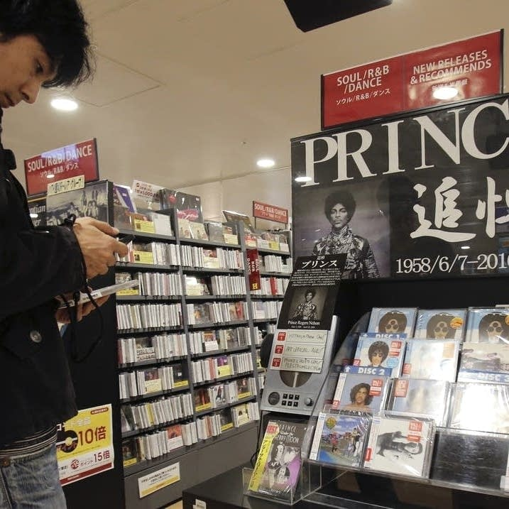 A customer looks at a CD of Prince's music